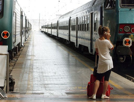 "<div class=""meta ""><span class=""caption-text "">A woman talks on a cellphone as she waits for a train at the railway station in Milan, Italy,  Friday, July 22, 2011. Italian commuters and tourists scrambled on Friday to negotiate a hodgepodge of bus, subway and train cancellations to get to their destinations during a one-day nationwide transport strike. National and local unions protesting a stalemate in collective contract talks shut down buses, subways and trains throughout the country. The unions complain that management has not seriously bargained in the nearly four years since the last contract expired, and that workers' salaries are losing buying power. In Rome, Milan and other major cities, transport companies guaranteed a minimum service during peak commute hours. (AP Photo/Luca Bruno) (AP Photo/ Luca Bruno)</span></div>"