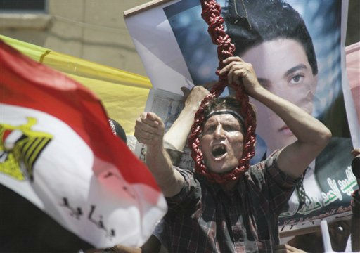 "<div class=""meta ""><span class=""caption-text "">An Egyptian holds a noose as he shouts revenge slogans in front of a a poster showing Ahmed Khalifa, one of hundreds who were killed during Egypt's Jan. 25th uprising,  at Tahrir Square, the focal point of the Egyptian uprising, in Cairo, Egypt, Friday, July 22, 2011. Protesters were vowing they would not leave the square until Egypt's temporary military rulers purge the remnants of Hosni Mubarak's deposed regime. Egyptian flag seen at left, Arabic read "" martyer Ahmed Khalifa"".   (AP Photo/Amr Nabil) (AP Photo/ Amr Nabil)</span></div>"