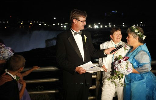 Kitty Lambert, right, and Cheryle Rudd are married by Niagara Falls Mayor Paul Dyster, left, in Niagara Falls, N.Y., Saturday, July 23, 2011.With a rainbow-lit Niagara Falls as a backdrop early Sunday, Lambert, 54, and Rudd, 53, were among the first gay couples to tie the knot with the blessing of the state, which last month became the sixth and largest to sanction gay marriage.  &#40;AP Photo&#47;David Duprey&#41; <span class=meta>(AP Photo&#47; David Duprey)</span>