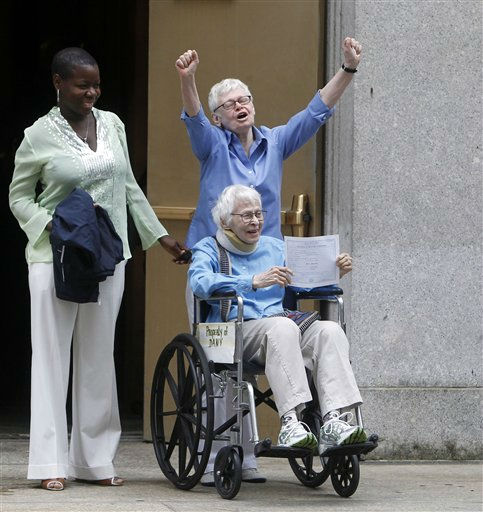 Phyllis Siegel, 76, arms raised, and Connie Kopelov, 84, in wheelchair, both of New York, celebrate after becoming the first same-sex couple to get married at the Manhattan City Clerk&#39;s office, Sunday, July 24, 2011, in New York. &#40;AP Photo&#47;Jason DeCrow&#41; <span class=meta>(AP Photo&#47; Jason DeCrow)</span>
