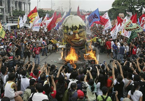 Protesters burn an effigy of Philippine President Benigno Aquino III which is shaped into a rotten egg ahead of the president&#39;s annual state of the nation address at suburban Quezon city northeast of Manila, Philippines, Monday July 25, 2011. Thousands of mostly left-wing protesters marched in the capital to demand higher wages, farmland and the prosecution of the President&#39;s predecessor for alleged graft. &#40;AP Photo&#47;Bullit Marquez&#41; <span class=meta>(AP Photo&#47; Bullit Marquez)</span>