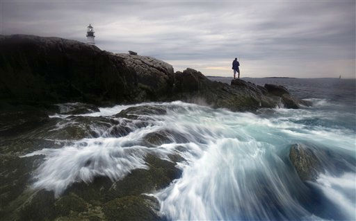 The surf crashes on the rocks around Sima Simic, of Portland, Maine, while fishing for striped bass below Portland Head Light at Fort Williams Park in Cape Elizabeth, Maine, Monday, July 25, 2011. &#40;AP Photo&#47;Robert F. Bukaty&#41; <span class=meta>(AP Photo&#47; Robert F. Bukaty)</span>