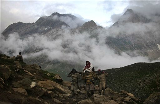In this photo dated 27 July 2011, a Hindu pilgrim is carried on a palanquin by porters on her way to the Amarnath cave shrine at Sheeshnag,  140 kilometers &#40;87 miles&#41; from Srinagar,India. At least half a million devotees make the pilgrimage to the icy cave which lies 13,500 feet &#40;4,115 meters&#41; above sea level in Indian-controlled Kashmir amid tight security. Hindus worship a stalagmite inside the cave as an incarnation of the Lord Shiva, the Hindu god of destruction and regeneration. &#40;AP Photo&#47;Altaf Qadri&#41; <span class=meta>(AP Photo&#47; Altaf Qadri)</span>