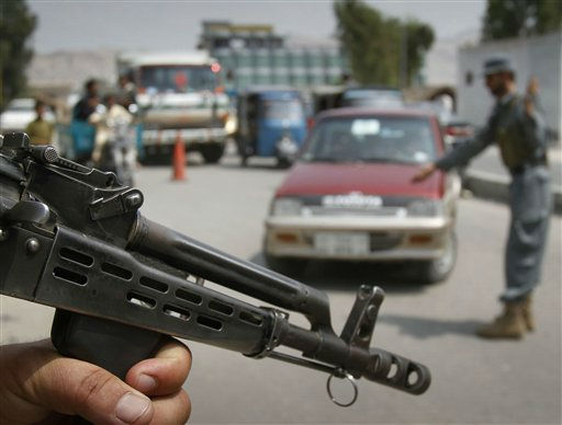 "<div class=""meta ""><span class=""caption-text "">An Afghan police officer, right, stops a car for searching at a temporary checkpoint in Jalalabad, Nangarhar province east of Kabul, Afghanistan, Tuesday, July 26, 2011. Afghanistan's President Hamid Karzai has told his country's soldiers and police that they face a difficult year ahead as they take on more security responsibilities,  but he wants them to push ahead so that Afghanistan can eventually defend itself. (AP Photo/Rahmat Gul) (AP Photo/ Rahmat Gul)</span></div>"