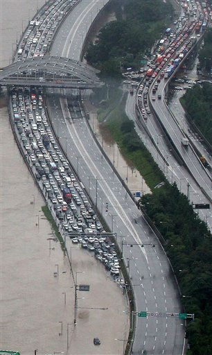 Vehicles are stalled on Olympic Road, the capital&#39;s main road, after heavy rain in Seoul, South Korea, Wednesday, July 27, 2011. A quick blast of heavy rain sent landslides barreling through South Korea&#39;s capital and a northern town Wednesday, killing dozens of people, officials said. &#40;AP Photo&#47;Yonhap, Jeon su-young&#41; KOREA OUT <span class=meta>(AP Photo&#47; Jeon Su-young)</span>