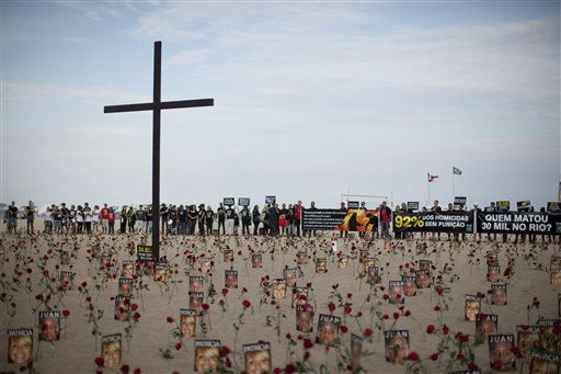People gather around a cross, flowers and photos of people who were killed during a protest against Impunity at Copacabana beach in Rio de Janeiro, Brazil, Sunday, July 31, 2011. Rio de Janeiro, that will host the 2016 Olympic Games, has one of the deadliest police forces on the planet and in the last five years, officers in Rio have killed on average 3.5 people per day, according to an Associated Press analysis of police data. &#40;AP Photo&#47;Felipe Dana&#41; <span class=meta>(AP Photo&#47; Felipe Dana)</span>