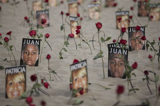 Roses stand on the sand next to photos of victims of violence during a protest against Impunity at Copacabana beach in Rio de Janeiro, Brazil, Sunday, July 31, 2011. Rio de Janeiro, that will host the 2016 Olympic Games, has one of the deadliest police forces on the planet and in the last five years, officers in Rio have killed on average 3.5 people per day, according to an Associated Press analysis of police data. &#40;AP Photo&#47;Felipe Dana&#41; <span class=meta>(AP Photo&#47; Felipe Dana)</span>