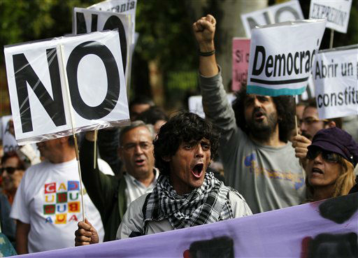 "<div class=""meta image-caption""><div class=""origin-logo origin-image ""><span></span></div><span class=""caption-text"">Protestors holds a banner reading: ""Democracy"" as they prepare to march to parliament to protest against austerity measures announced by the Spanish government in Madrid, Spain, Tuesday, Sept. 25, 2012. Spain's Parliament has taken on the appearance of a heavily guarded fortress with dozens of police blocking access from every possible angle, hours ahead of a protest against the conservative government's handling of the economic crisis. The demonstration, organized behind the slogan 'Occupy Congress,' is expected to draw thousands of people. The protestors call for Parliament to be dissolved and fresh elections held, claiming the government's austerity measures show the ruling Popular Party misled voters to get elected last November. (AP Photo/Andres Kudacki) (AP Photo/ Andres Kudacki)</span></div>"