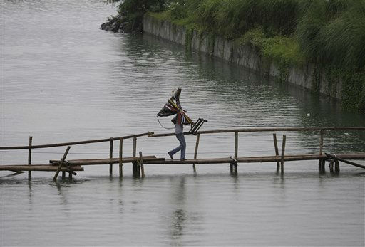 A Filipino vendor crosses a bamboo bridge to sell belts in suburban Paranaque, south of Manila, Philippines on Monday, Aug. 1, 2011. &#40;AP Photo&#47;Aaron Favila&#41; <span class=meta>(AP Photo&#47; Aaron Favila)</span>