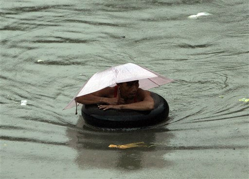 A man uses a floater as he negotiates a chest-deep flood water Tuesday, Aug. 2, 2011 in suburban Quezon City, north of Manila, Philippines. A powerful typhoon is blowing away from the northern Philippines after killing at least four people even though it did not make landfall. &#40;AP Photo&#47;Pat Roque&#41; <span class=meta>(AP Photo&#47; Pat Roque)</span>