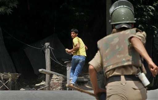 An Indian policeman chases a Kashmiri protester during a protest in Srinagar, India, Wednesday, Aug. 3, 2011. Kashmiris shut down shops and businesses Wednesday in a general strike to protest a man&#39;s death in police custody in the Indian-controlled portion of the disputed Himalayan region. &#40;AP Photo&#47;Mukhtar Khan&#41; <span class=meta>(AP Photo&#47; Mukhtar Khan)</span>