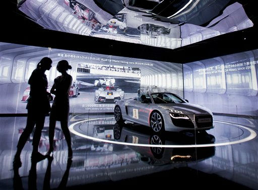 A model chats with a visitor next to a new Audi R8 convertible on display during a show in Beijing Thursday, Aug. 4, 2011. &#40;AP Photo&#47;Andy Wong&#41; <span class=meta>(AP Photo&#47; Andy Wong)</span>