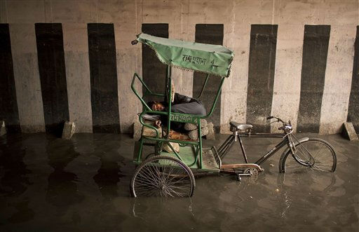An Indian bicycle rickshaw puller sleeps after stopping in a water-logged underpass during monsoon rain in New Delhi, India, Thursday, Aug. 4, 2011. India receives the annual monsoon rains from June to September. &#40;AP Photo&#47;Kevin Frayer&#41; <span class=meta>(AP Photo&#47; Kevin Frayer)</span>