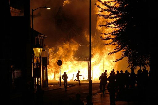 A shop is set on fire as rioters gather  in Croydon, south London, Monday, Aug. 8, 2011. Violence and looting spread across some of London&#39;s most impoverished neighborhoods on Monday, with youths setting fire to shops and vehicles, during a third day of rioting in the city that will host next summer&#39;s Olympic Games. &#40;AP Photo&#47;Sang Tan&#41; <span class=meta>(AP Photo&#47; Sang Tan)</span>