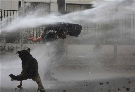 A demonstrator is sprayed by a police water cannon during riots after a student protest in Santiago, Tuesday, Aug. 9, 2011. Students in Chile marched by the tens of thousands to keep pressure on the government for profound changes in public education. &#40;AP Photo&#47;Sebastian Silva&#41; <span class=meta>(AP Photo&#47; Sebastian Silva)</span>