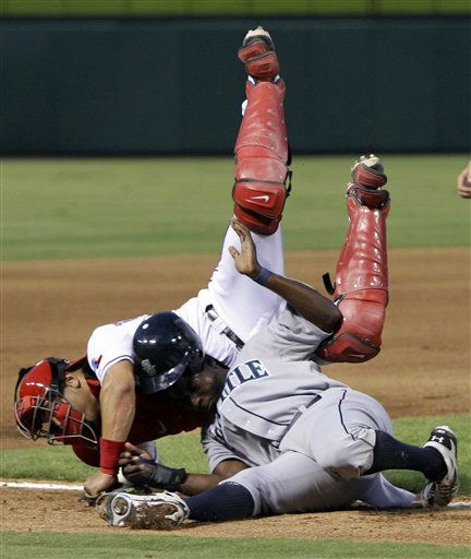 Texas Rangers catcher Yorvit Torrealba, top, flips over Seattle Mariners&#39; Trayvon Robinson in a rundown between third and home in the fourth inning of a baseball game on Wednesday, Aug. 10, 2011, in Arlington, Texas. Robinson was trying to advance home on a Luis Rodriguez fielder&#39;s choice. &#40;AP Photo&#47;Tony Gutierrez&#41; <span class=meta>(AP Photo&#47; Tony Gutierrez)</span>