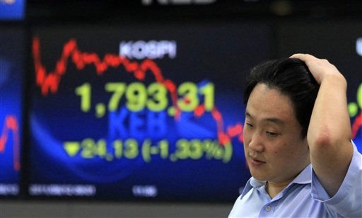 A currency trader works in front of  a screen showing the Korea Composite Stock Price Index at the Korea Exchange Bank headquarters in Seoul, South Korea, Friday, Aug. 12, 2011.  Asian stock markets struggled to find their footing Friday, giving back morning gains despite a dramatically higher finish on Wall Street prompted by a slight drop in U.S. unemployment claims. The Korea Composite Stock Price Index fell 1.33 percent, or 24.13, to close at 1,793.31.&#40;AP Photo&#47;Ahn Young-joon&#41; <span class=meta>(AP Photo&#47; Ahn Young-joon)</span>