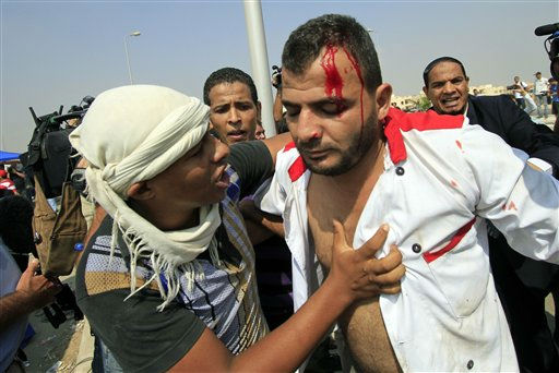 "<div class=""meta ""><span class=""caption-text "">An injured man is comforted after clashes between supporters of Egypt's ousted President Hosni Mubarak and anti-Mubarak protesters outside a police academy during a court hearing for the former president in Cairo, Egypt, Monday Aug. 15, 2011. Former President Hosni Mubarak returned to court Monday for the second session of his trial on charges of corruption and complicity in killing protesters during the mass uprising that ousted him from power. The ailing, 83-year old Mubarak arrived in a helicopter from a Cairo hospital where he has been held since his first court appearance on Aug. 3 at a police academy that once been named after him. He was then wheeled into the metal defendants' cage on a bed with his two sons, Gamal and Alaa, by his side. The sons are facing only corruption charges.(AP Photo/Khalil Hamra) (AP Photo/ Khalil Hamra)</span></div>"