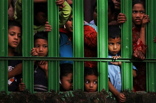 "<div class=""meta ""><span class=""caption-text "">In this Monday, Aug. 15, 2011 photo, children watch, from behind a fence, the Deopokhari festival in Khokana, Katmandu, Nepal. The festival is held to appease, what locals believe is, a demon in the pond. Every year on this day cattle is sacrificed to the pond demon so that no human lives are lost drowning in the pond, what locals allege was a common occurrence before the festival began. (AP Photo/Niranjan Shrestha) INDIAN SUB CONTINENT OUT (AP Photo/ Niranjan Shrestha)</span></div>"