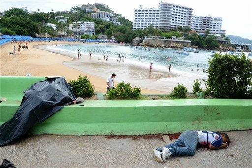 EDITORS NOTE GRAPHIC CONTENT - The bodies of two men shot dead next to the Caleta beach,  background,  lie, one of them covered,  in the Pacific resort city of Acapulco, Mexico, Tuesday Aug. 16, 2011. The city of Acapulco has been hit by violence as drug gangs continue to battle for control of the region. &#40;AP Photo&#47;Bernandino Hernandez&#41; <span class=meta>(AP Photo&#47; Bernandino Hernandez)</span>