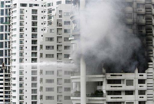 Thai firefighter on a ladder spray water on smoke coming out from the 18th floor of a 30-story condominium where a fire broke out on Wednesday Aug. 17, 2011. Police said at least three people were injured in the afternoon blaze. No death was reported. &#40;AP Photo&#47;Sakchai Lalit&#41; <span class=meta>(AP Photo&#47; SAKCHAI LALIT)</span>