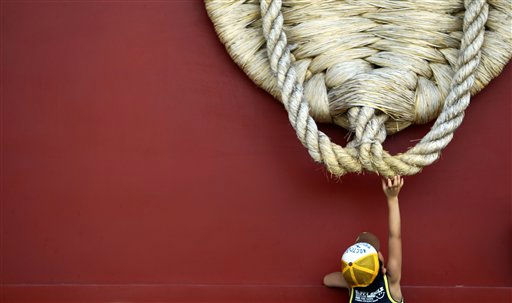 "<div class=""meta ""><span class=""caption-text "">A child reaches out to touch a huge straw sandal dedicated to a Buddhist temple in Tokyo Wednesday, Aug. 17, 2011. (AP Photo/Junji Kurokawa) (AP Photo/ Junji Kurokawa)</span></div>"