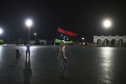 Akman Mohammad, 78, holds a pre-Moammar Gadhafi flag as he takes part in a demonstration to celebrate the recent advances in the battle front and the six-month anniversary of the uprising against Gadhafi&#39;s regime at the rebel-held town of Benghazi, Libya, late Wednesday, Aug. 17, 2011. &#40;AP Photo&#47;Alexandre Meneghini&#41; <span class=meta>(AP Photo&#47; Alexandre Meneghini)</span>
