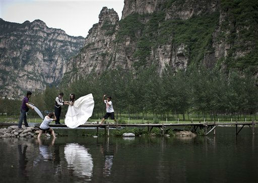 A photographer takes pictures of a newlyweds couple posing against the scenic spot at Shidu, on the outskirts of Beijing, China, Thursday, Aug. 18, 2011. Shidu, which means &#34;10 ferry crossings&#34; in Chinese, is one of the most famous tourist attractions in the country. &#40;AP Photo&#47;Andy Wong&#41; <span class=meta>(AP Photo&#47; Andy Wong)</span>