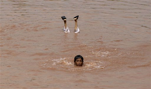 Pakistani boys swim in a puddle of rain water to cool off as the temperature rises on the outskirts of Islamabad, Pakistan, Friday, Aug. 19, 2011. &#40;AP Photo&#47;Muhammed Muheisen&#41; <span class=meta>(AP Photo&#47; Muhammed Muheisen)</span>