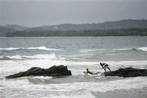 Surfers?jump off the rocks into the ocean as?tropical storm?Irene approaches to the island in Luquillo, Puerto Rico, Sunday, August 21, 2011. The storm, packing winds of about 50 mph &#40;85 kph&#41; and tracking westward at 20 mph &#40;32 kph&#41;, was expected to strengthen and pass near the U.S. island of Puerto Rico later Sunday or early Monday. &#40;AP Photo&#47;Ricardo Arduengo&#41; <span class=meta>(AP Photo&#47; Ricardo Arduengo)</span>
