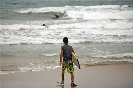 A surfer?walks into the ocean as?tropical storm?Irene approaches to the island in Luquillo, Puerto Rico, Sunday, Aug. 21, 2011. The storm, packing winds of about 50 mph &#40;85 kph&#41; and tracking westward at 20 mph &#40;32 kph&#41;, was expected to strengthen and pass near the U.S. island of Puerto Rico later Sunday or early Monday. &#40;AP Photo&#47;Ricardo Arduengo&#41; <span class=meta>(AP Photo&#47; Ricardo Arduengo)</span>