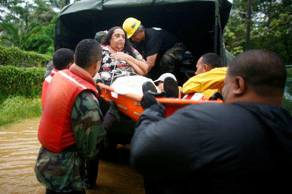 A woman is carried on a stretcher by civil defense workers after she was unable to attend a respiratory therapy due to an emphysema after hurricane Irene struck and flooded the area she lives in Naguabo, Puerto Rico, Monday, Aug. 22, 2011. (AP Photo/Ricardo Arduengo)