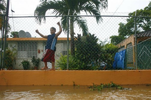 "<div class=""meta ""><span class=""caption-text "">A child walks hanging from a fence outside his flooded house after hurricane Irene hit the area in Naguabo, Puerto Rico, Monday, Aug. 22, 2011. (AP Photo/Ricardo Arduengo) (AP Photo/ Ricardo Arduengo)</span></div>"