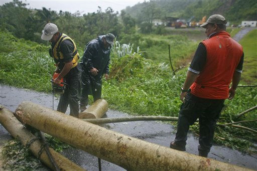 "<div class=""meta ""><span class=""caption-text "">Civil defense workers remove fallen trees from a road after hurricane Irene hit the area in Naguabo, Puerto Rico, Monday, Aug. 22, 2011. Hurricane Irene headed out over warm ocean water on a path that could take it to northeastern Dominican Republic and part of Haiti early Tuesday and to the U.S. mainland by the end of the week. (AP Photo/Ricardo Arduengo) (AP Photo/ Ricardo Arduengo)</span></div>"