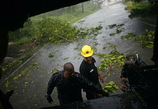 Civil defense workers prepare to remove debris from a road after hurricane Irene hit the area in Naguabo, Puerto Rico, Monday, Aug. 22, 2011. Hurricane Irene headed out over warm ocean water on a path that could take it to northeastern Dominican Republic and part of Haiti early Tuesday and to the U.S. mainland by the end of the week. &#40;AP Photo&#47;Ricardo Arduengo&#41; <span class=meta>(AP Photo&#47; Ricardo Arduengo)</span>
