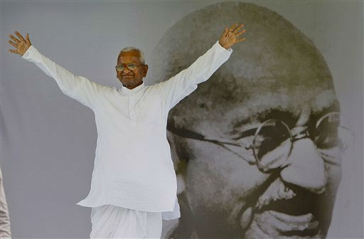 Anti-corruption activist Anna Hazare acknowledges the crowd as he returned to the stage after a break, in front of the portrait of Mahatma Gandhi at the Ramlila Grounds in New Delhi, India, Monday, Aug. 22, 2011. Hazare, who has entered the seventh day of his fast, is unhappy with the Indian government&#39;s response, aides said Monday, as Prime Minister Manmohan Singh appeared staunch against caving to the activist&#39;s demands for a powerful anti-graft watchdog office. &#40;AP Photo&#47;Gurinder Osan&#41; <span class=meta>(AP Photo&#47; Gurinder Osan)</span>