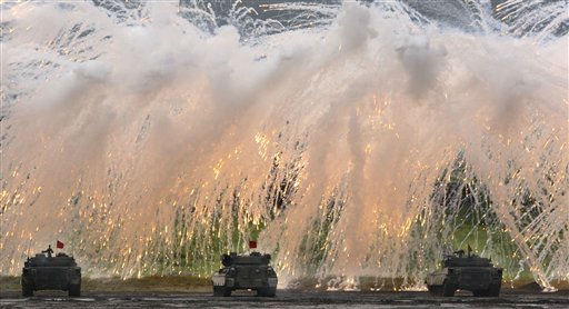 A line of Japan Ground Self-Defense Force tanks flare up a smoke screen during the annual live-firing exercise and demonstration at Higashi Fuji training range in Gotemba, northwest of Tokyo, Tuesday, Aug. 23, 2011. &#40;AP Photo&#47;Koji Sasahara&#41; <span class=meta>(AP Photo&#47; Koji Sasahara)</span>