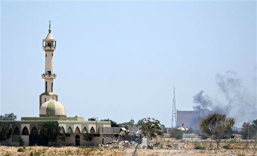 "<div class=""meta ""><span class=""caption-text "">Smoke rises over buildings in the main compound of Moammar Gadhafi in the Bab Al-Aziziya district in Tripoli, Tuesday, Aug. 23, 2011. Thick clouds of gray and white smoke filled the sky as heavy gunfire and explosions shook several districts of the city of 2 million people. Some of the heaviest fighting was around Gadhafi's main compound and military barracks. The compound, which has been heavily damaged by NATO airstrikes, has emerged as one of the centers of government resistance since tanks rolled out and began firing at rebels trying to get in.(AP Photo/Sergey Ponomarev) (AP Photo/ Sergey Ponomarev)</span></div>"