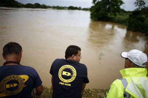 Civil defense workers watch from a bridge as La Plata River overflows its banks, flooding the area the day after hurricane Irene hit in Toa Baja, Puerto Rico, Tuesday, Aug. 23, 2011.   Irene grew into a Category 2 hurricane late Monday and the U.S. National Hurricane Center in Miami said it could reach Category 3 as early as Tuesday and possibly become a monster Category 4 storm within 72 hours. Irene is on a track that could see it reach the U.S. Southeast as a major storm by the end of the week. &#40;AP Photo&#47;Ricardo?Arduengo&#41; <span class=meta>(AP Photo&#47; Ricardo Arduengo)</span>