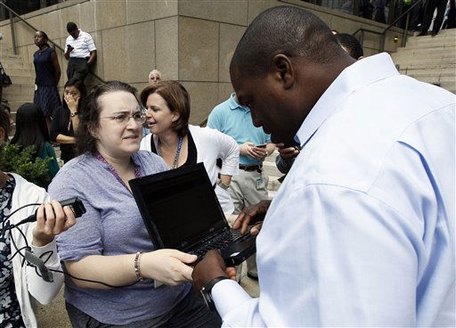"<div class=""meta ""><span class=""caption-text "">Kerry Schlueter, left, holds a laptop computer for Damon Watts as he tries to find information on an earthquake that was felt in Baltimore on Tuesday, Aug. 23, 2011 while waiting outside of an office building. Downtown office buildings were cleared and workers were waiting for clearance to re-enter. (AP Photo/Patrick Semansky) (AP Photo/ Patrick Semansky)</span></div>"