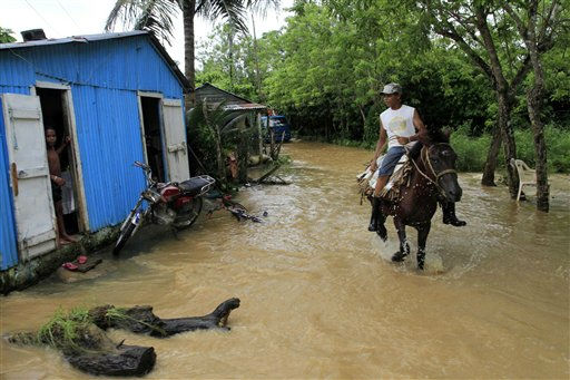 A resident rides a horse through a flooded neighborhood after the passing of Hurricane Irene in Nagua on the northern coast of the Dominican Republic, Tuesday Aug. 23, 2011.  Hundreds were displaced by flooding in the Dominican Republic, forced to take refuge in churches, schools or relatives&#39; homes. Electricity also was cut in some areas. &#40;AP Photo&#47;Roberto Guzman&#41; <span class=meta>(AP Photo&#47; Roberto Guzman)</span>