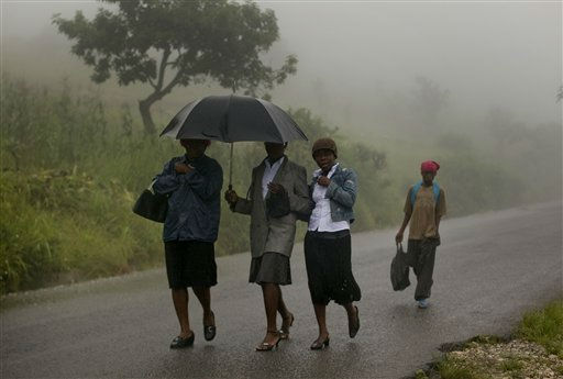 ORRECTION TO CLARIFY  EFFECTS OF HURRICANE IRENE IN HAITI - People walk on the road between Gonaives and Cap Haitien under the rain from the outer bands of Hurricane Irene in Haiti, Tuesday Aug. 23, 2011. Irene was still lashing the northern coasts of Haiti and the Dominican Republic, where crews have begun cleaning up debris and the government warned of flooding. It was forecast to pass over or near the Turks and Caicos Islands and the southeastern Bahamas by Tuesday night and be near the central Bahamas early Wednesday. &#40;AP Photo&#47;Ramon Espinosa&#41; <span class=meta>(AP Photo&#47; Ramon Espinosa)</span>