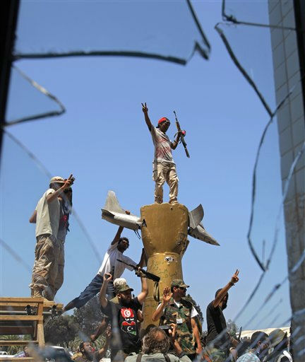 Rebel fighters celebrate as they stand on top of the monument inside the main Moammar Gadhafi compound in Bab Al-Aziziya in Tripoli, LIbya, Wednesday, Aug. 24, 2011. The rebels say they have now taken control of nearly all of Tripoli, but sporadic gunfire could still be heard Wednesday, and Gadhafi loyalists fired shells and assault rifles at fighters who had captured the Libyan leader&#39;s personal compound one day earlier. &#40;AP Photo&#47;Sergey Ponomarev&#41; <span class=meta>(AP Photo&#47; Sergey Ponomarev)</span>