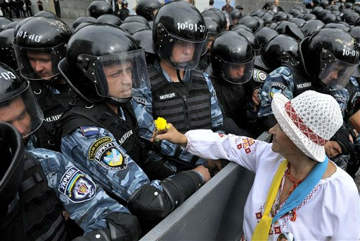 An opposition activist gives a flower to police officers as they block a march marking the 20th anniversary of Ukraine&#39;s independence from the Soviet Union and protest the arrest of former Prime Minister Yulia Tymoshenko as Ukrainian riot police officers block  in Kiev, Ukraine, Wednesday, Aug. 24, 2011. Over 5,000 opposition activists rallied Wednesday to mark the 20th anniversary of Ukraine&#39;s independence from the Soviet Union and protest the arrest of former Prime Minister Yulia Tymoshenko.&#40;AP Photo&#47;Andriy Kravchenko&#41; <span class=meta>(AP Photo&#47; Andriy Kravchenko)</span>