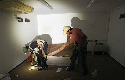 "<div class=""meta ""><span class=""caption-text "">Rebel fighters search a room in the bunker of the main Moammar Gadhafi compound in Bab Al-Aziziya in Tripoli, LIbya, Thursday, Aug. 25, 2011. Libya's rebel leadership has offered a 2 million dollar bounty on Gadhafi's head, but the autocrat has refused to surrender as his 42-year regime crumbles, fleeing to an unknown destination. Speaking to a local television channel Wednesday, apparently by phone, Gadhafi vowed from hiding to fight on ""until victory or martyrdom."" (AP Photo/Sergey Ponomarev) (AP Photo/ Sergey Ponomarev)</span></div>"