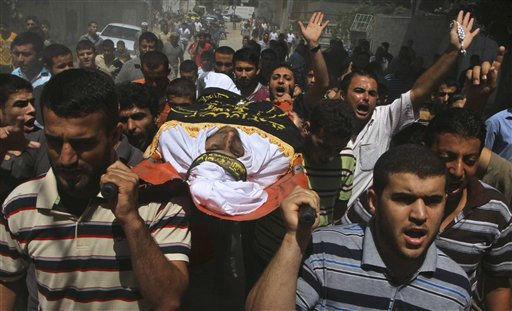 Palestinians carry the body of Islamic Jihad militant Ateya Mkat, 22, killed in an Israeli air strike Wednesday, during his funeral in Gaza City, Thursday, Aug. 25, 2011. Palestinian official said that the militant was killed during an Israeli air strike late Wednesday. Palestinian militants fired rocket barrages that wounded an Israeli baby Wednesday, and Israel retaliated with airstrikes that killed four Gaza fighters, Gaza officials said. &#40;AP Photo&#47;Ashraf Amra&#41; <span class=meta>(AP Photo&#47; Ashraf Amra)</span>