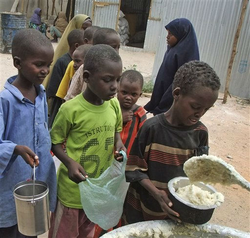 Somali children from southern Somalia are given cooked food at a distribution center in Mogadishu, Somalia, Thursday, Aug. 25, 2011. The United Nations says famine will probably spread to all of southern Somalia within a month and force tens of thousands more people to flee into the capital of Mogadishu. &#40;AP Photo&#47;Farah Abdi Warsameh&#41; <span class=meta>(AP Photo&#47; Farah Abdi Warsameh)</span>