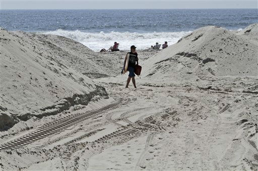 A surfer walks past sand dunes built to hold the surf back in preparation for Hurricane Irene,  Friday, Aug. 26, 2011 in Long Beach, N.Y.  Long Island residents in the path of Irene girded for wind, rain and flooding as the storm stood poised to bear down on an already saturated New York state.&#40;AP Photo&#47;Mary Altaffer&#41; <span class=meta>(AP Photo&#47; Mary Altaffer)</span>