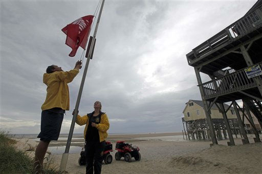 Nags Head Ocean Rescue lifeguards Ben Mechak, left, an Erika Audfroid hoist a no swimming flag in Nags Head, N.C., Friday, Aug. 26, 2011 as Hurricane Irene takes aim at the North Carolina coast.  The full force of Hurricane Irene was still a day away from the East Coast but heightened waves began hitting North Carolina&#39;s Outer Banks early Friday.  &#40;AP Photo&#47;Gerry Broome&#41; <span class=meta>(AP Photo&#47; Gerry Broome)</span>