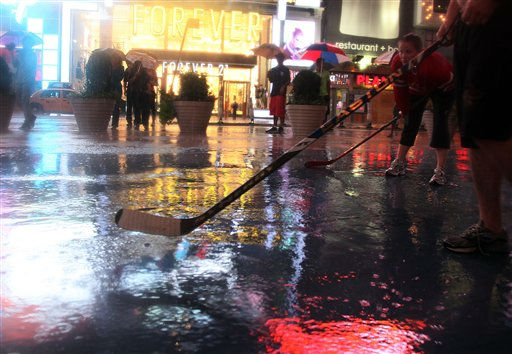 "<div class=""meta image-caption""><div class=""origin-logo origin-image ""><span></span></div><span class=""caption-text"">People gather in the rain to watch hockey players from Vancouver, British Columbia, during an impromptu game at Times Square in New York, late Saturday, Aug. 27, 2011, as Hurricane Irene approaches the region. Irene has the potential to cause billions of dollars in damage all along a densely populated arc that includes Washington, Baltimore, Philadelphia, New York, Boston and beyond. At least 65 million people could be affected. (AP Photo/Chelsea Matiash) (AP Photo/ Chelsea Matiash)</span></div>"